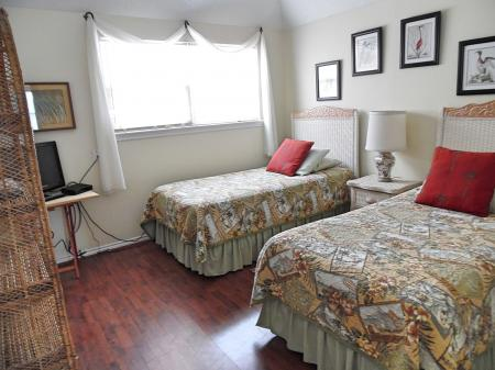 Click to enlarge image 2nd bedroom with tv and large closets - BeeGee's Redfish Quarters - Large 2 bedroom, 2.5 bath with tile and laminate floors, private laundry, Dog Friendly. Walk to the beach. Covered Patio.