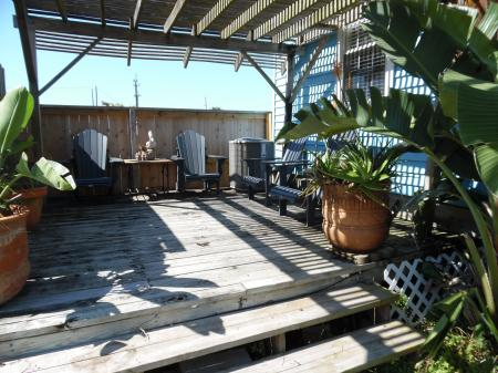 Click to enlarge image Lovely shaded deck at the back of the house - Palm Cottage - Old town cottage near historic downtown Port Aransas. Two bedrooms, one bath, small laundry, quaint and cute patio area. Dog Friendly