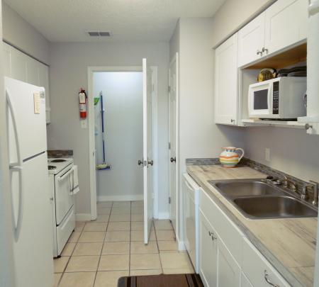 Click to enlarge image Looking at kitchen and laundry room - BeeGee's Tarpon Quarters - One bedroom, with king bed, one bath. LARGE condo with laundry, tile floors, Dog Friendly.Walk to the beach.