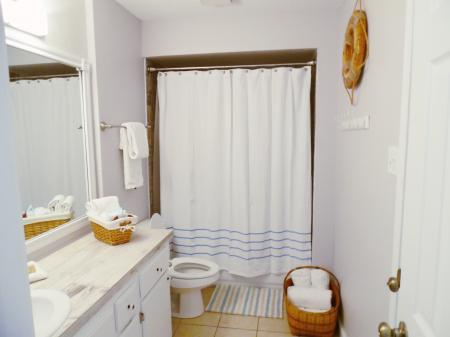 Click to enlarge image Bathroom with new tub and tiled surround - BeeGee's Wahoo Quarters - One bedroom, one bath, LARGE condo with laundry, tile floors, Dog Friendly. Walk to beach